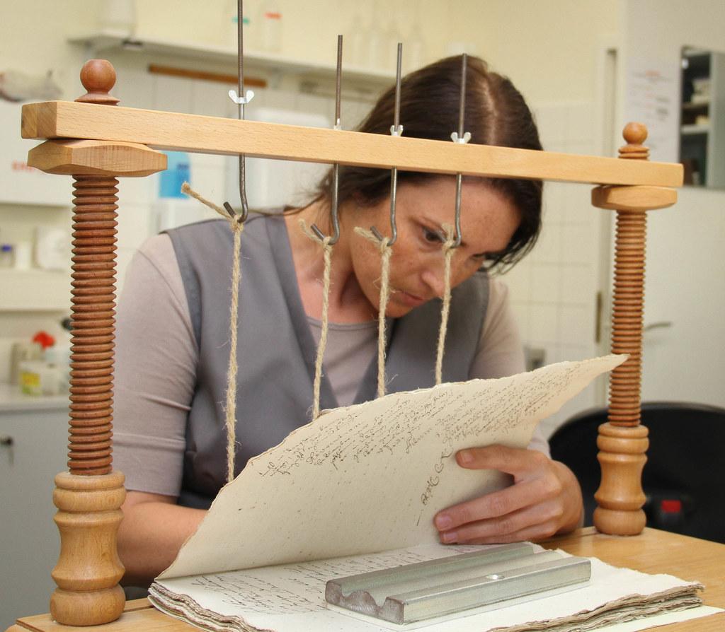 Sabrina Schaller bei der Arbeit an der Heftlade. Bücher und Schriften werden akr..