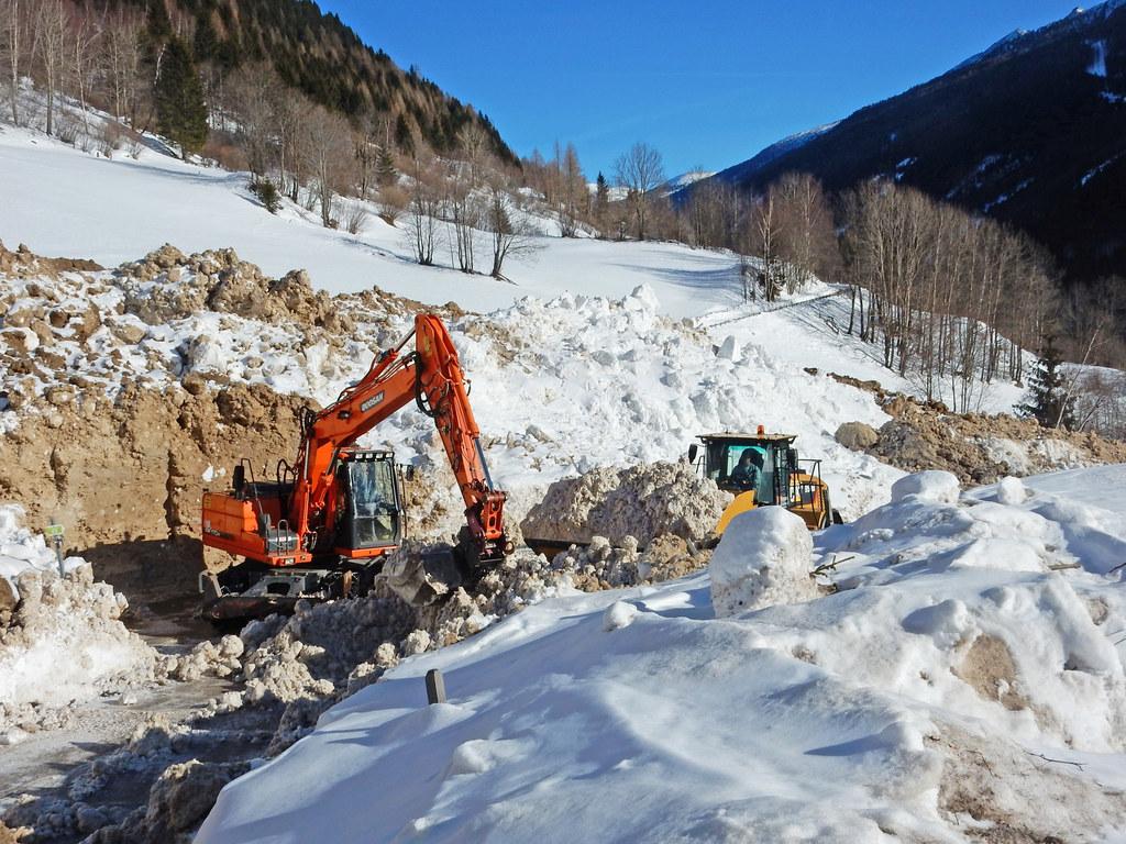 Mit schwerem Gerät werden die Schneemassen nach dem Lawinenabgang weggeräumt.