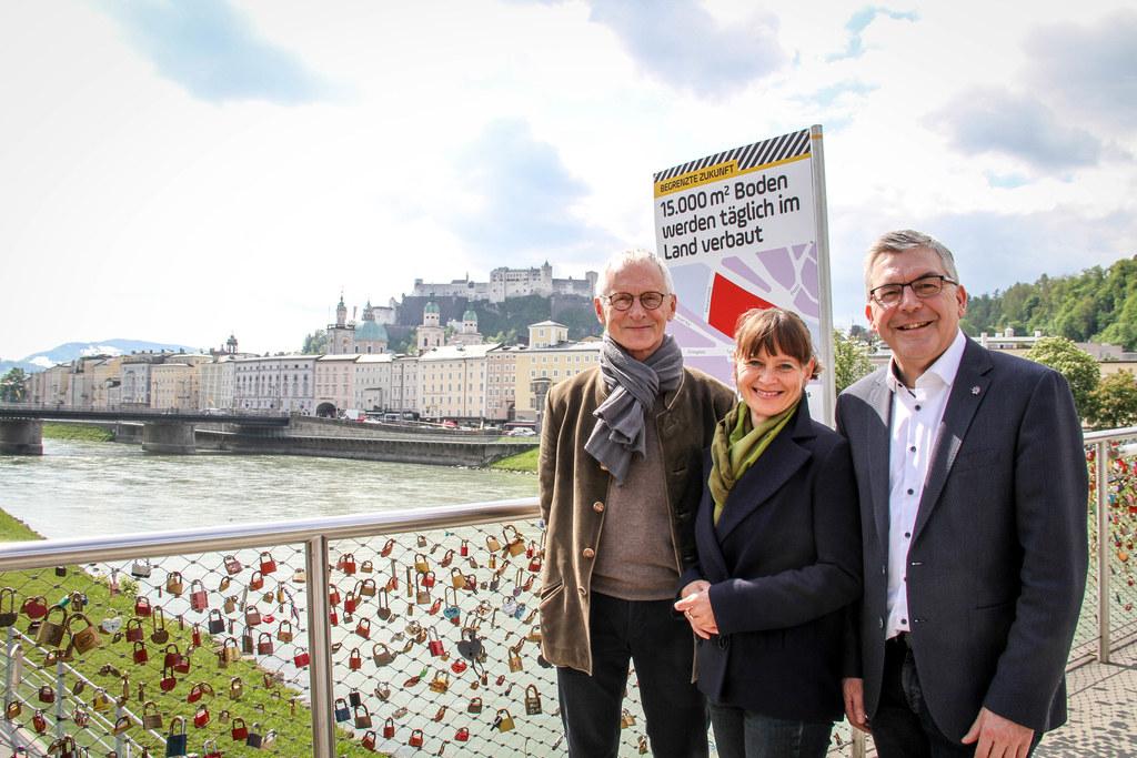 LR Josef Schwaiger, Stadträtin Martina Berthold und Naturschutzbund-Obmann Winfrid Herbst präsentieren die Ausstellung zum Thema Bodenschutz am Salzburger Makartsteg.