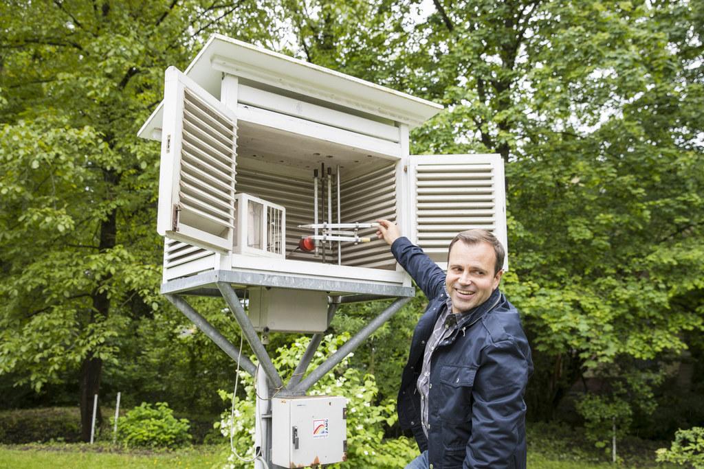 Meteorologe Alexander Ohms begutachtet die Wetterhütte. Der weiße Anstrich und die Luftschlitze bewirken, dass sich der Innenraum im Sommer möglichst wenig aufheizt.