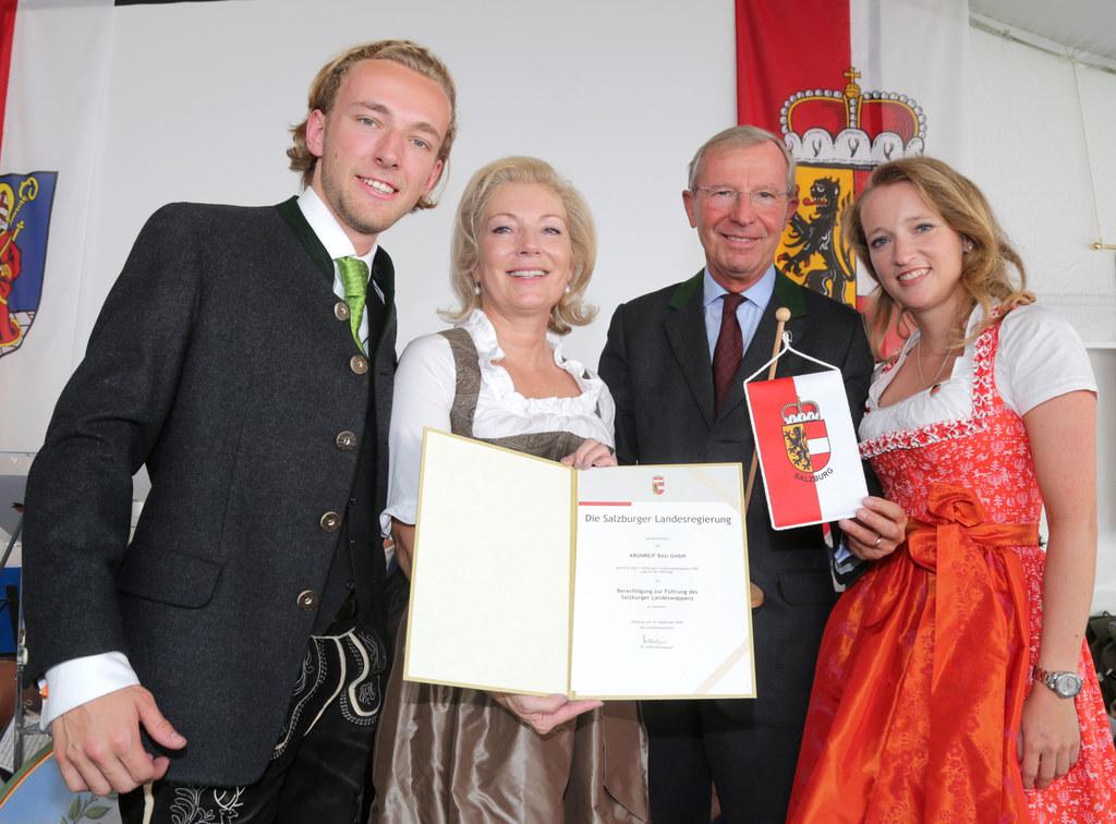 Ein Landeswappen zum Hunderter für Kronfreif Bau, v.l. Lukas Brunnauer, Firmenchefin Charlotte Brunnauer, LH Wilfried Haslauer und Lisa Brunnauer.