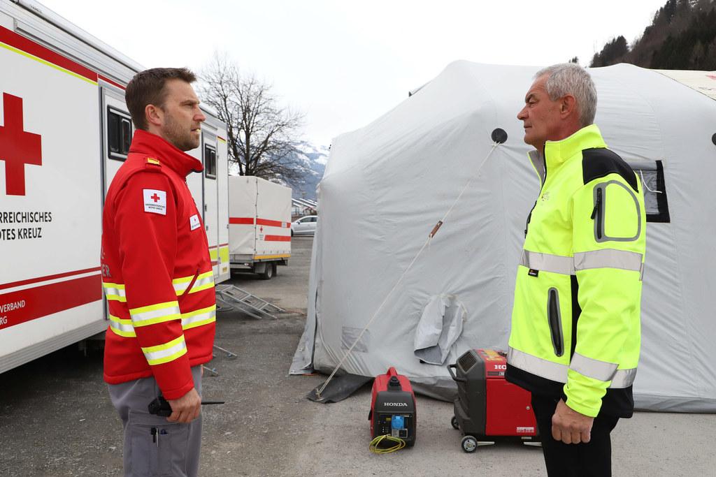 Bezirkshauptmann Bernhard Gratz im Gespräch mit einem Mitarbeiter des Roten Kreuzes.