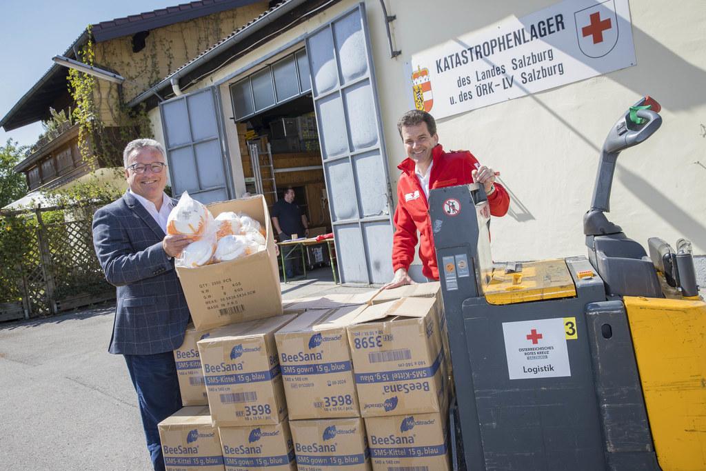 LH-Stv. Heinrich Schellhorn und Mathias Herbst vom ÖRK-Landesverband Salzburg mit den Schutzausrüstungen für Sozialeinrichtungen beim Katastrophenlager des Landes und des Roten Kreuzes.