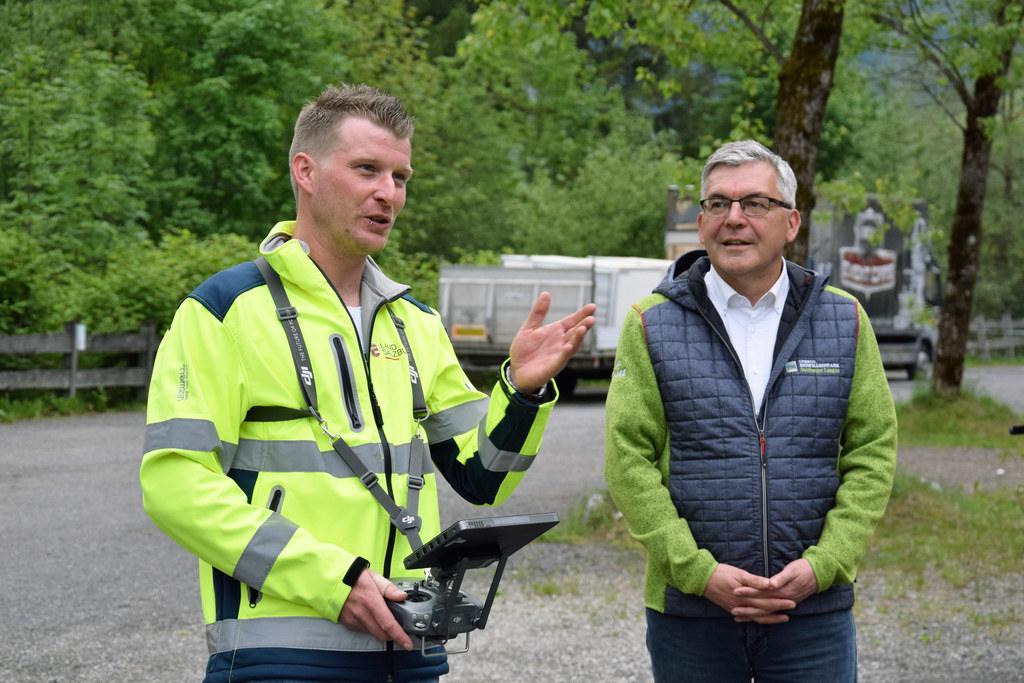 Drohnenpilot Martin Lausenhammer erläutert LR Josef Schwaiger die komplexe Steuerung der Videodrohne bei der Analyse von Unwetterschäden.