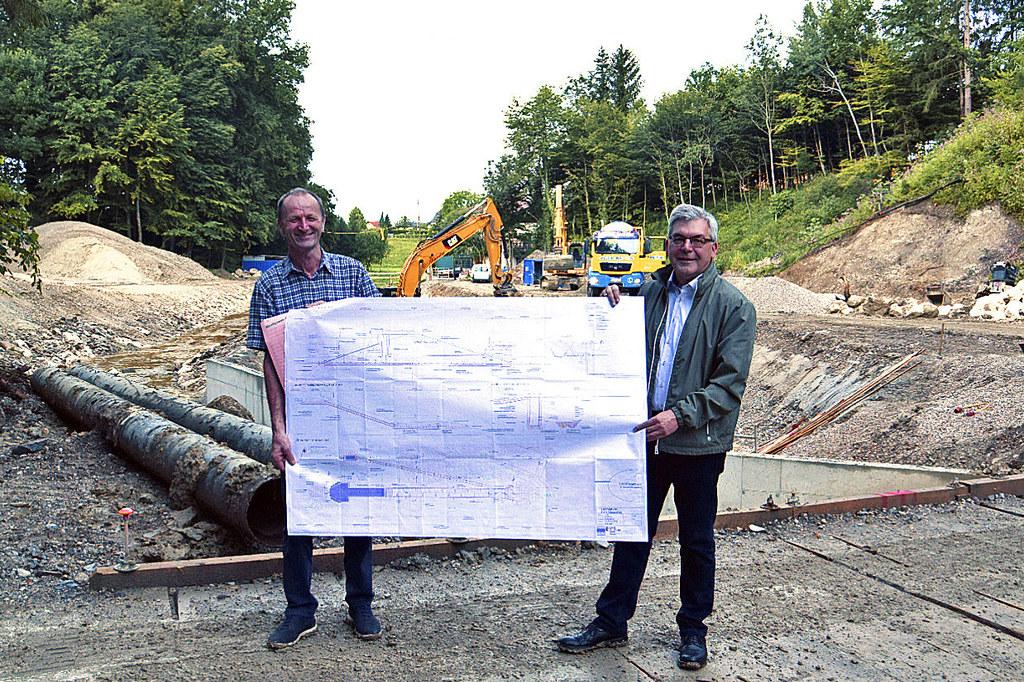 Bürgermeister Franz Gangl (St. Georgen) und LR Josef Schwaiger mit dem Bauplan für das neue Rückhaltebecken und den Schutzdamm am Pladenbach in St. Georgen. Im Zuge des Hochwasserschutzes wird der Bach im Ort noch aufgeweitet und renaturiert, damit Kinder wieder das Wasser erleben können.