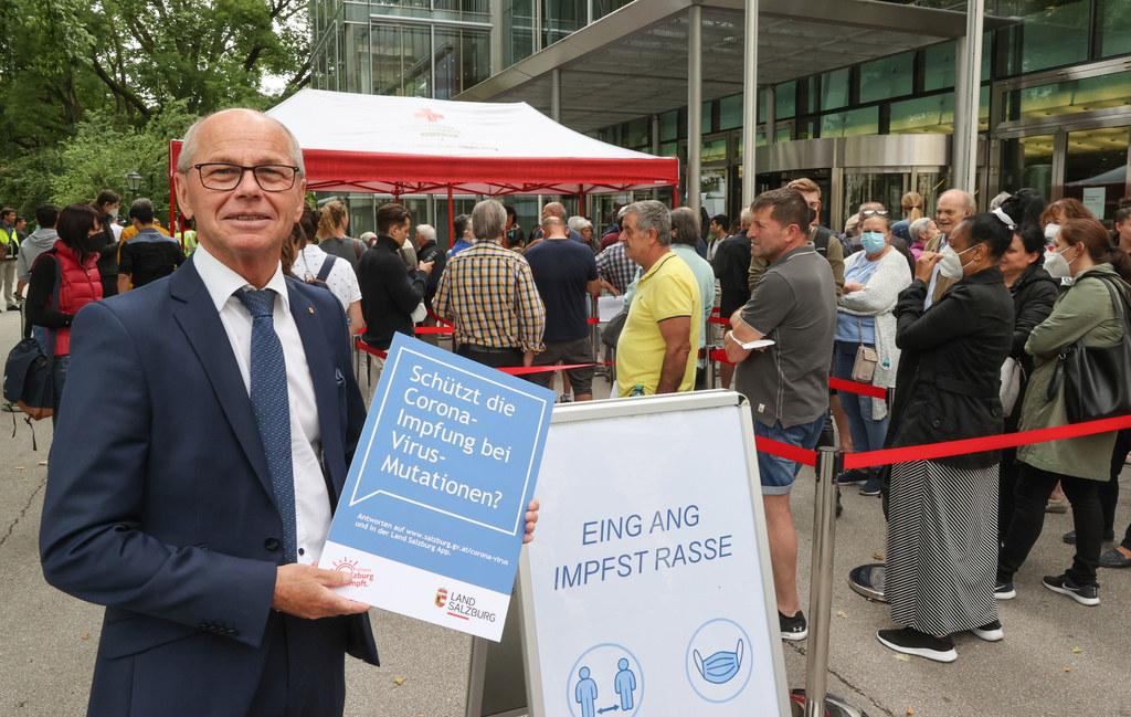 """Landes-hauptmann-Stell-vertreter Christian Stöckl sagt: """"Die Impfung schützt am besten gegen das Corona-Virus."""" Im Hintergrund stellen sich viele Menschen für eine Impfung im Salzburger Kongress-haus an."""