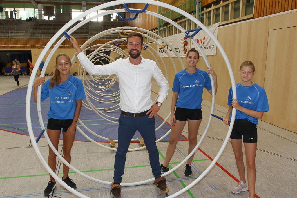 """Als begeisterter Fußballer probierte LR Stefan Schnöll bei einem seiner Besuche bei der Aktion """"Jugend zum Sport"""" im ULSZ Rif auch einmal das Rhönrad aus, assistiert von erfahrenen Trainerinnen (Archivbild)."""